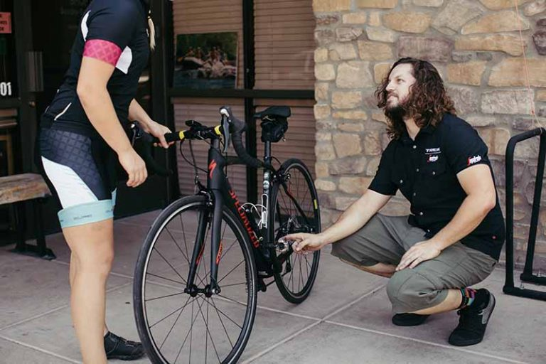 A man crouching next to a bicycle.
