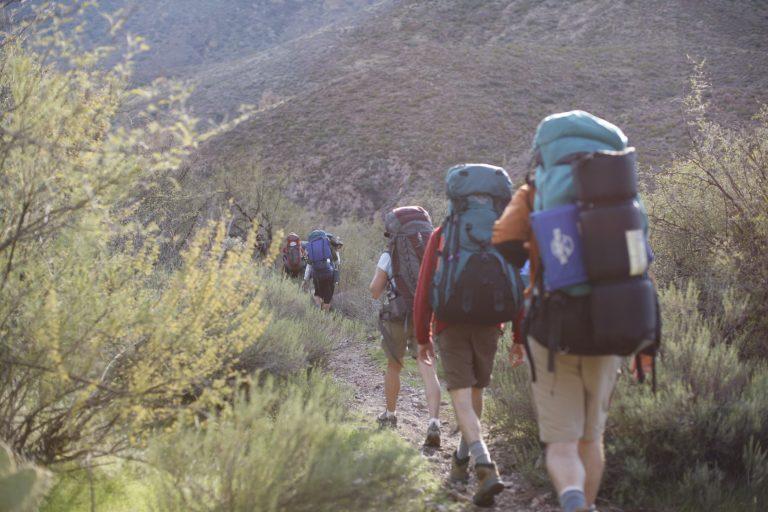 Five backpackers hiking.