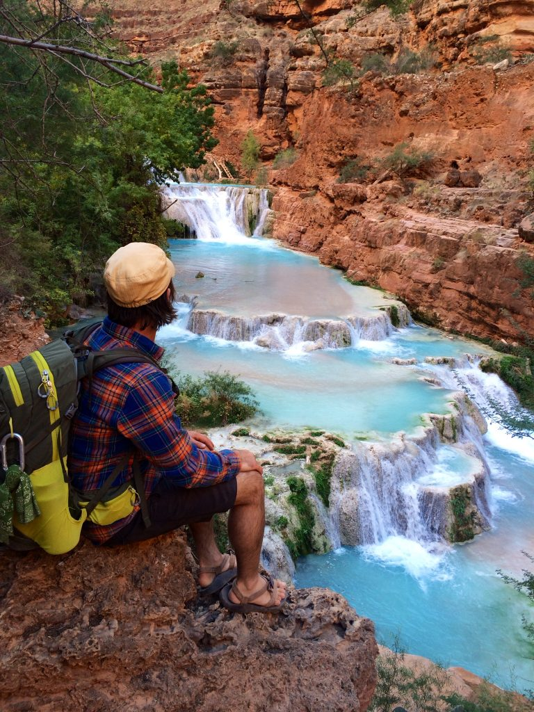 A person sitting and admiring a waterfall.