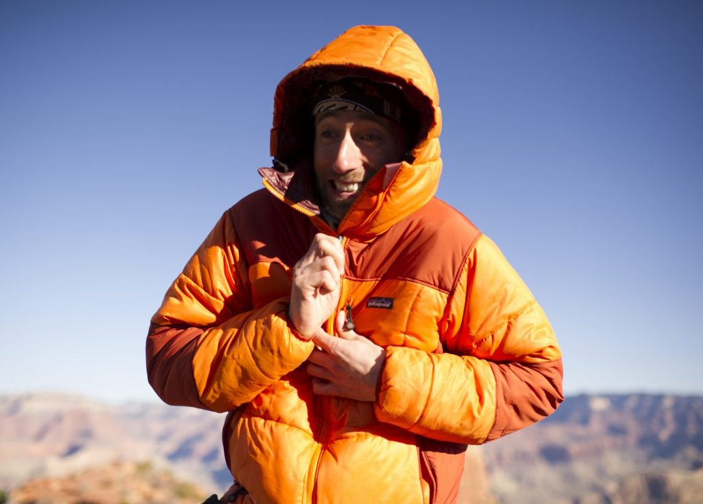 Hiker in orange parka in the Grand Canyon.