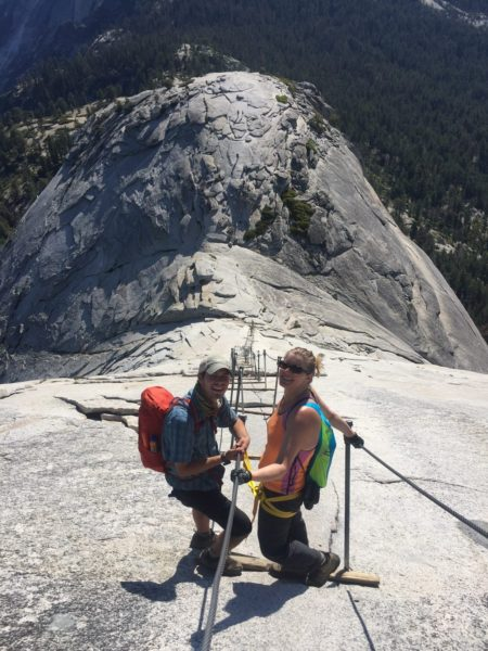 Two hikers hiking down Half Dome's cables.