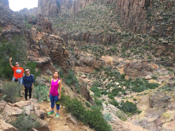 Three hikers stand for a photo amongst a canyon.