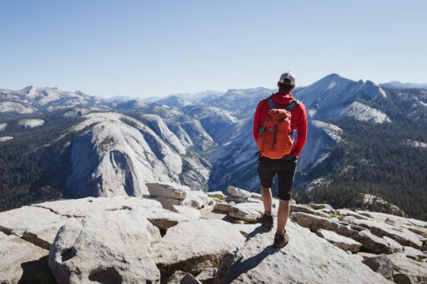 A person looking at the view from the top of Half Dome.