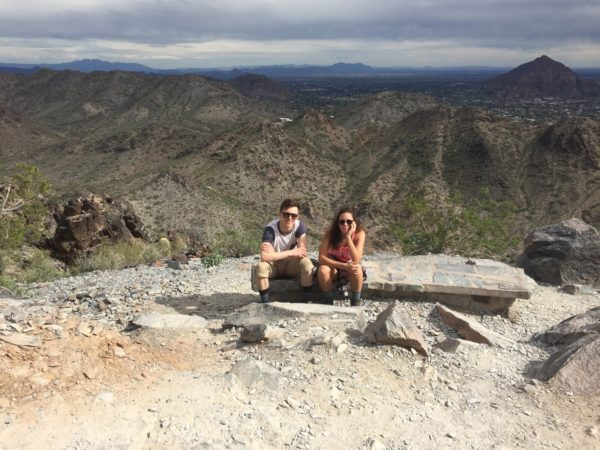 Two people sitting on a rock resting.