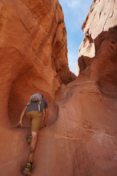 A person climbing up a rock formation.