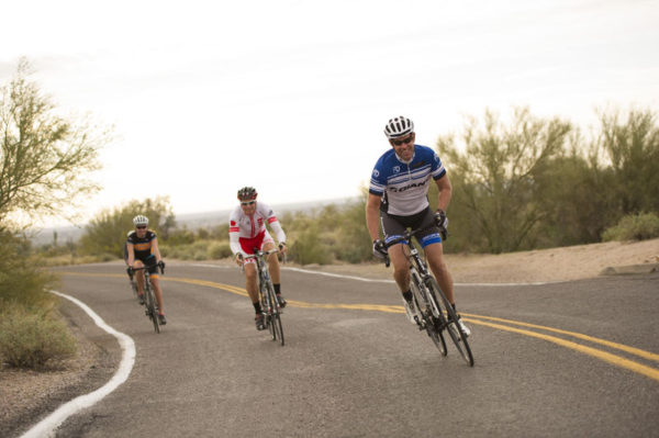 Three bicyclists riding on a road.