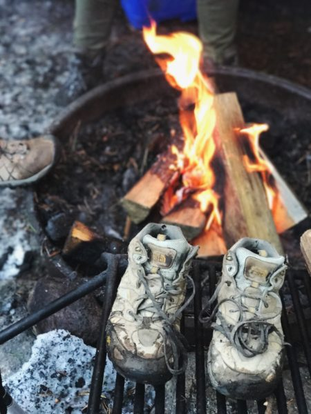 Shoes next to an open fire.