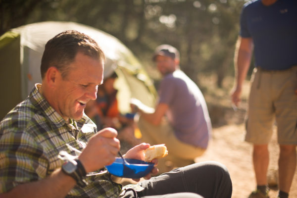 A man eating food while camping.