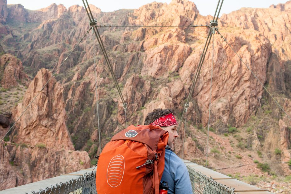 A man looking at the view from a bridge at the Grand Canyon.
