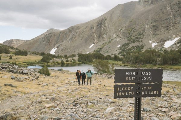 Three people posing behind a sign for Mono Pass.