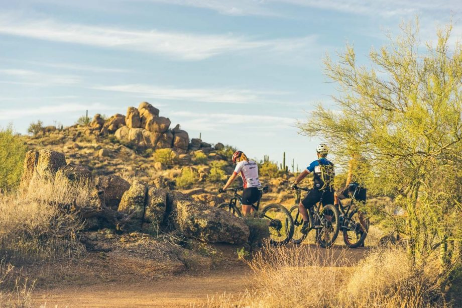 Cyclists pause near rocks on Arizona mountain bike trip
