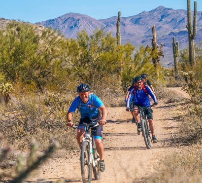 Cyclists speed along Arizona desert mountain bike tour trail