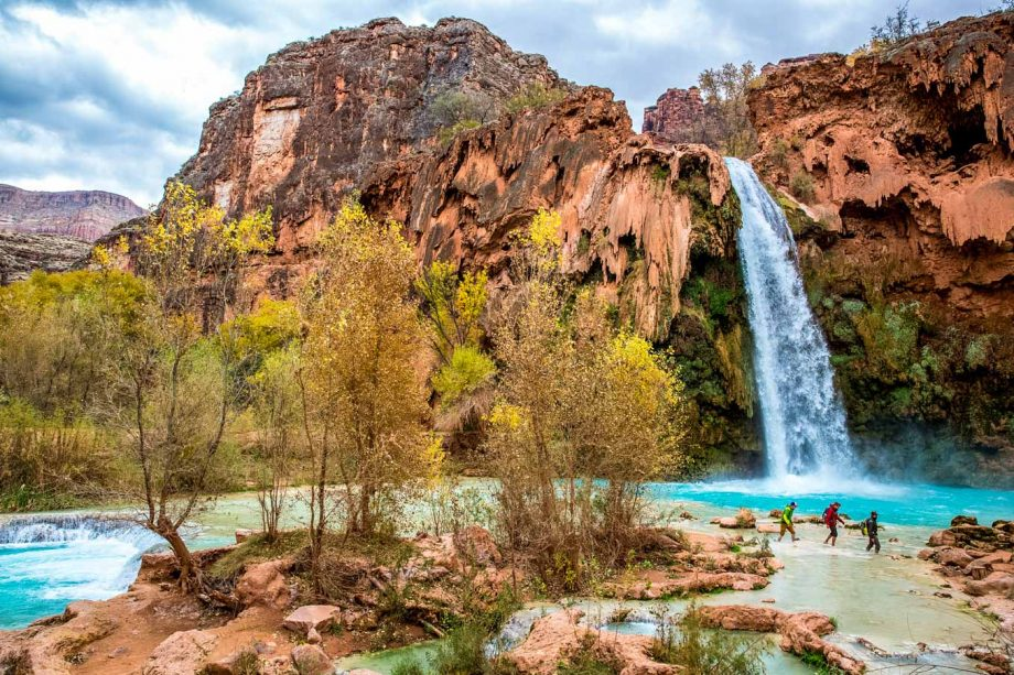 Hikers wade in Havasu Falls waterfall pool