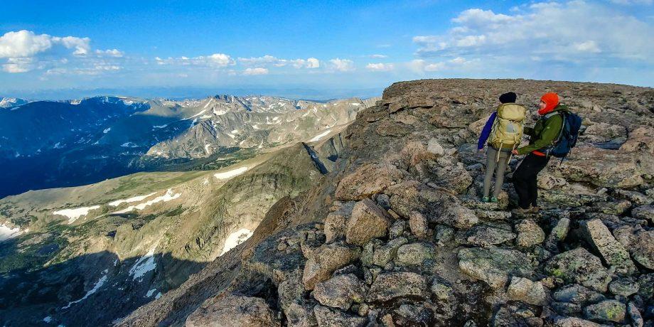 Hikers stand on rock overlook on Longs Peak backpacking trip