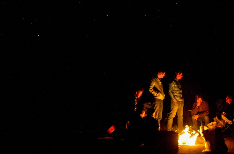 Campers next to fire under the stars on hiking trip