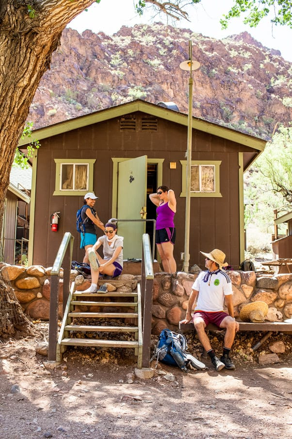 Hikers resting outside cabin on Grand Canyon Rim to Rim trip