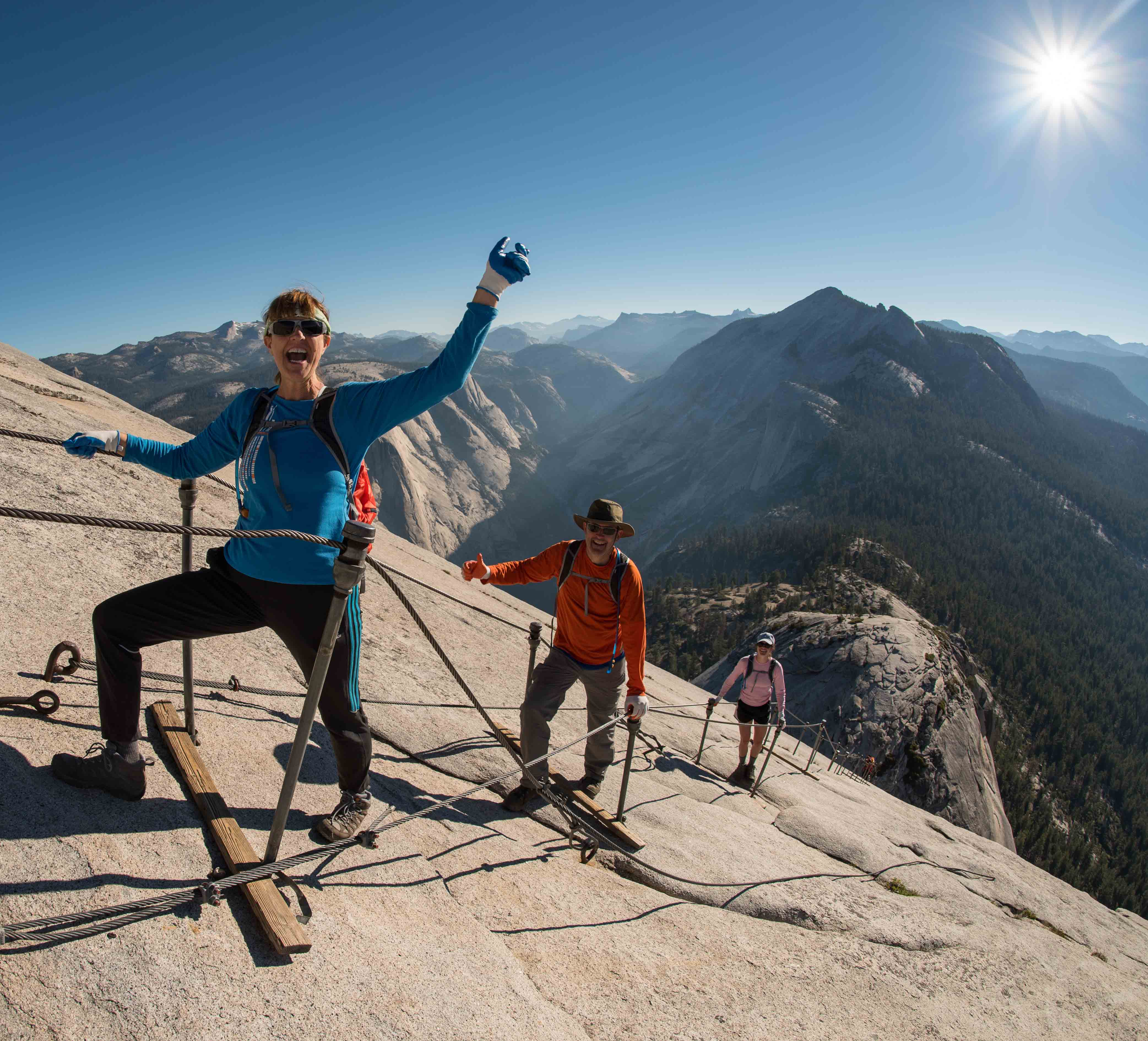 A woman summits Half Dome while hiking the cables