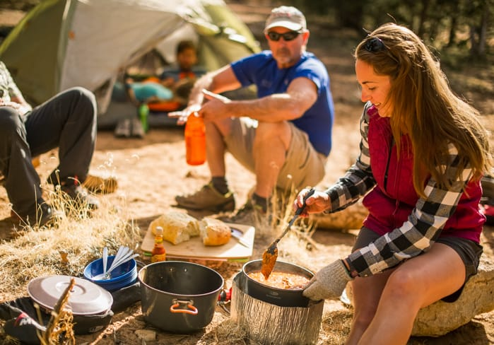 Camper cooks meal on overnight adventure trip