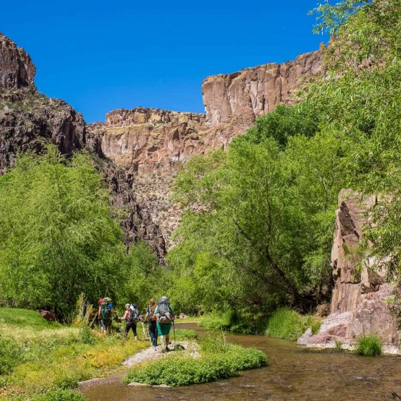 Hiking tour group crosses stream on Aravaipa Canyon trip