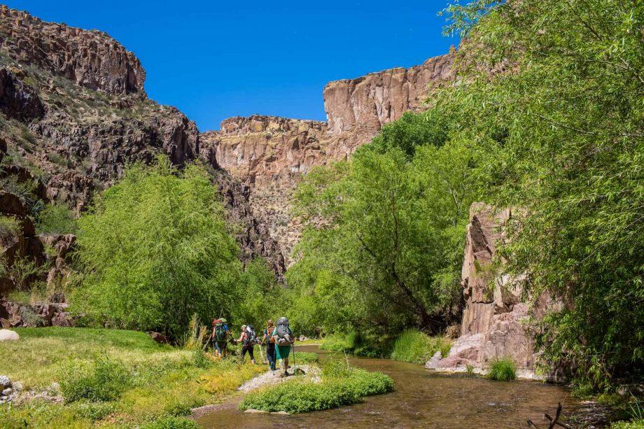 Hiking tour group crosses stream on Aravaipa Canyon trip