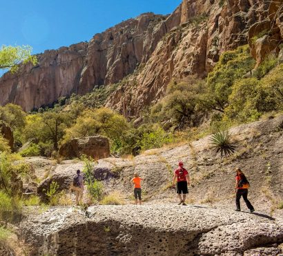 Hikers look up at Aravaipa Canyon cliff on backpacking tour