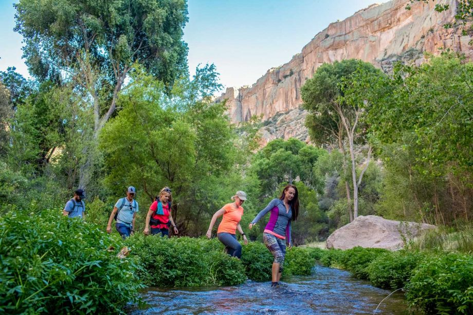Hiking group crosses river on Aravaipa Canyon river on backpacking trip
