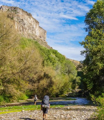 Hikers cross rocky stream on Aravaipa Canyon backpacking trip