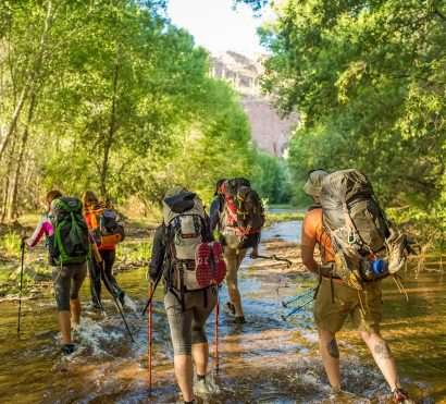 Hikers cross stream on Aravaipa Canyon backpacking tour