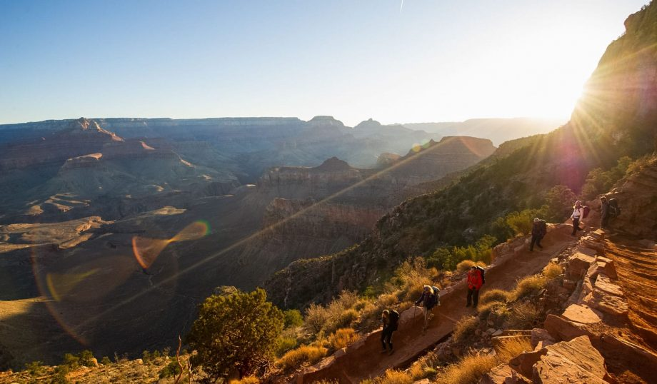Hiking group descends rocky trail on Grand Canyon trip at sunset
