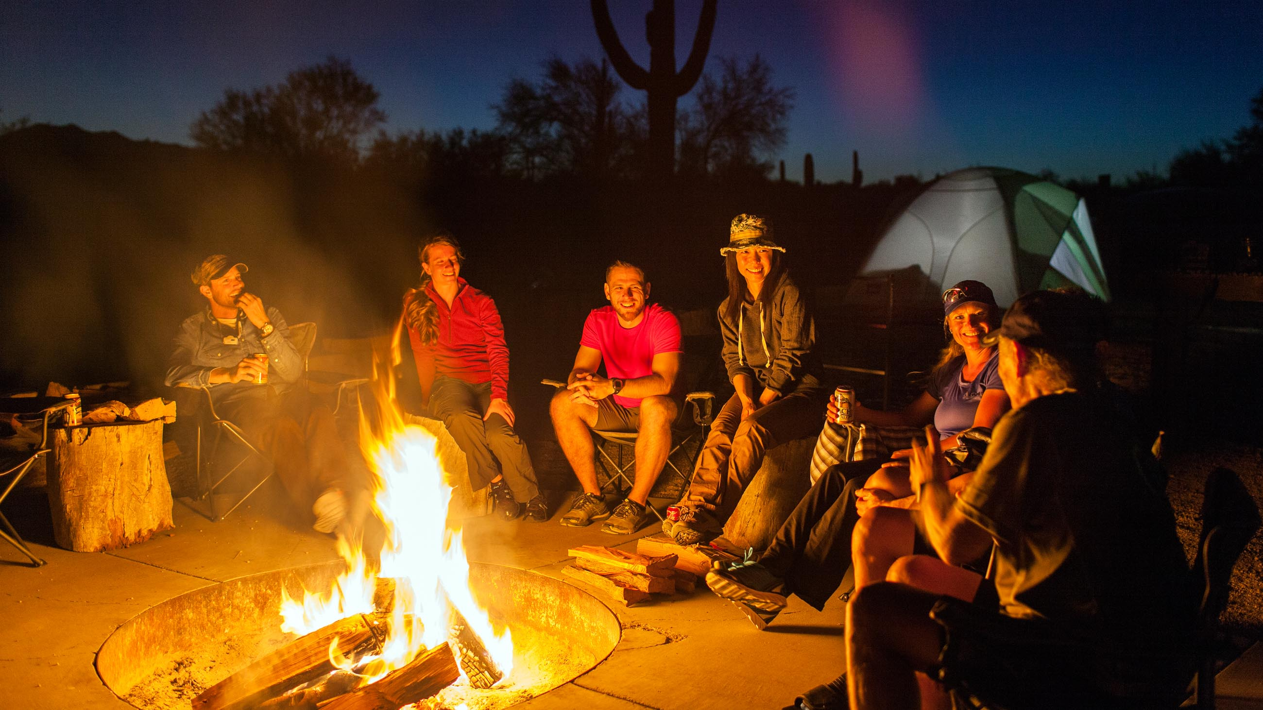 Smiling group sits by campfire on Arizona tour