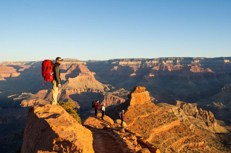 Hikers stand on cliff edge overlooking Grand Canyon sunset