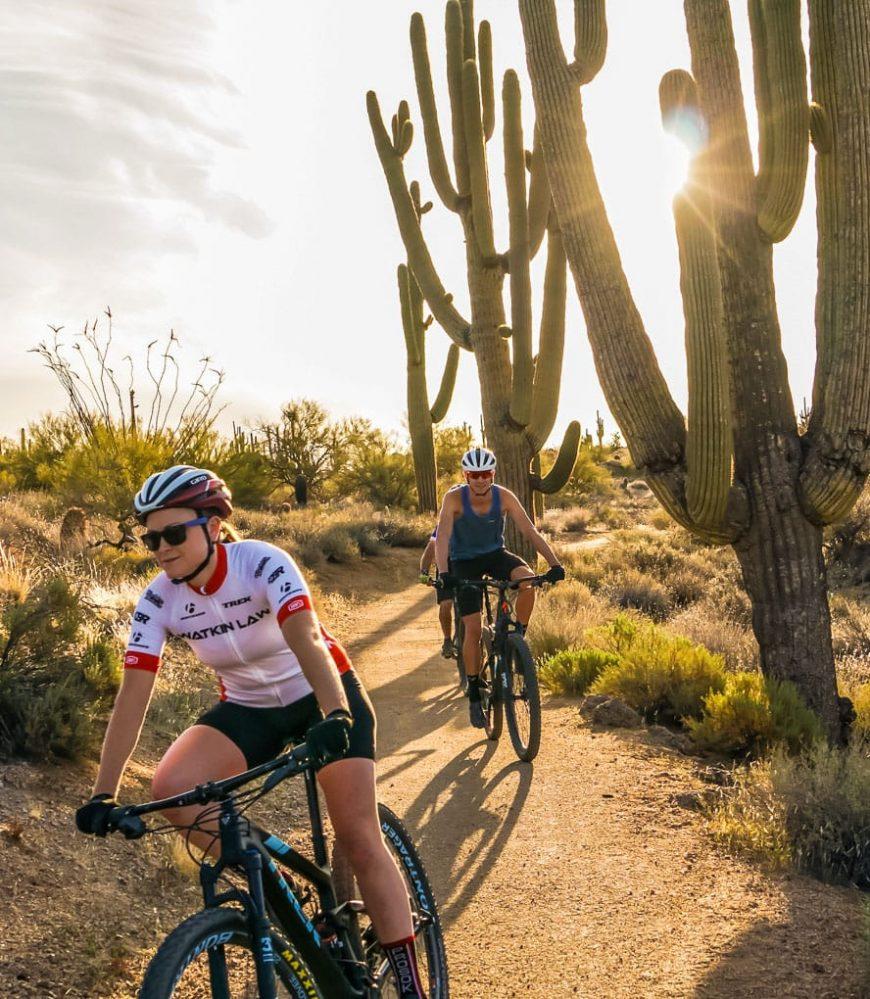 Cyclers next to cactus on Arizona desert mountain biking tour
