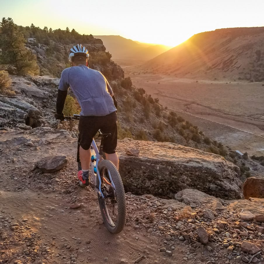 Mountain biker rides cliff at sunset on Gooseberry Mesa tour