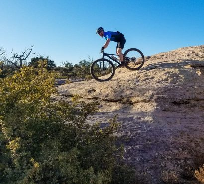 Mountain biker rides down rocks on Gooseberry Mesa trail