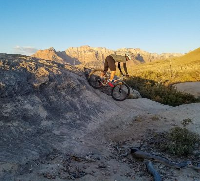 Cyclist navigates rocks on Gooseberry Mesa mountain bike trip