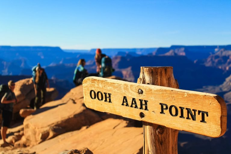 Hikers overlook Grand Canyon behind Ooh Aah Point sign.