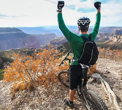 Mountain biker raises fists in front of Grand Canyon overlook