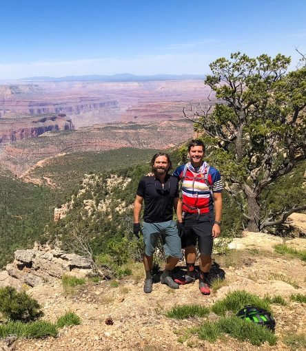 Mountain bikers stand in front of Grand Canyon overlook