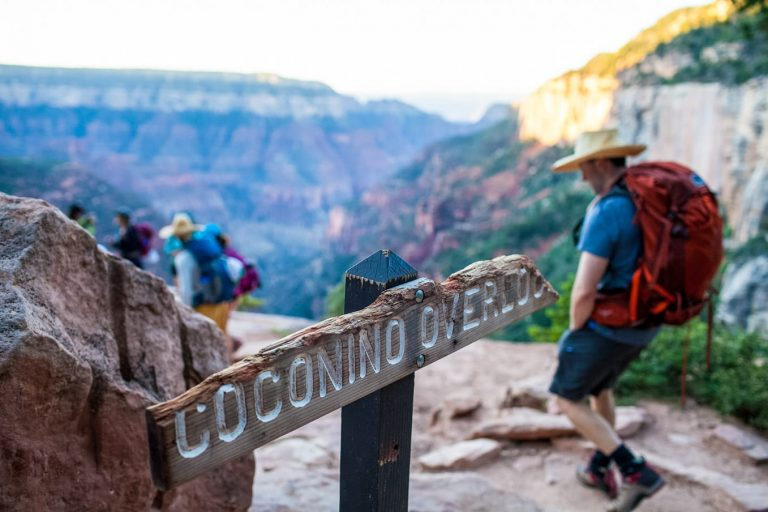 Hikers pass Coconino Overlook sign on Grand Canyon tour.