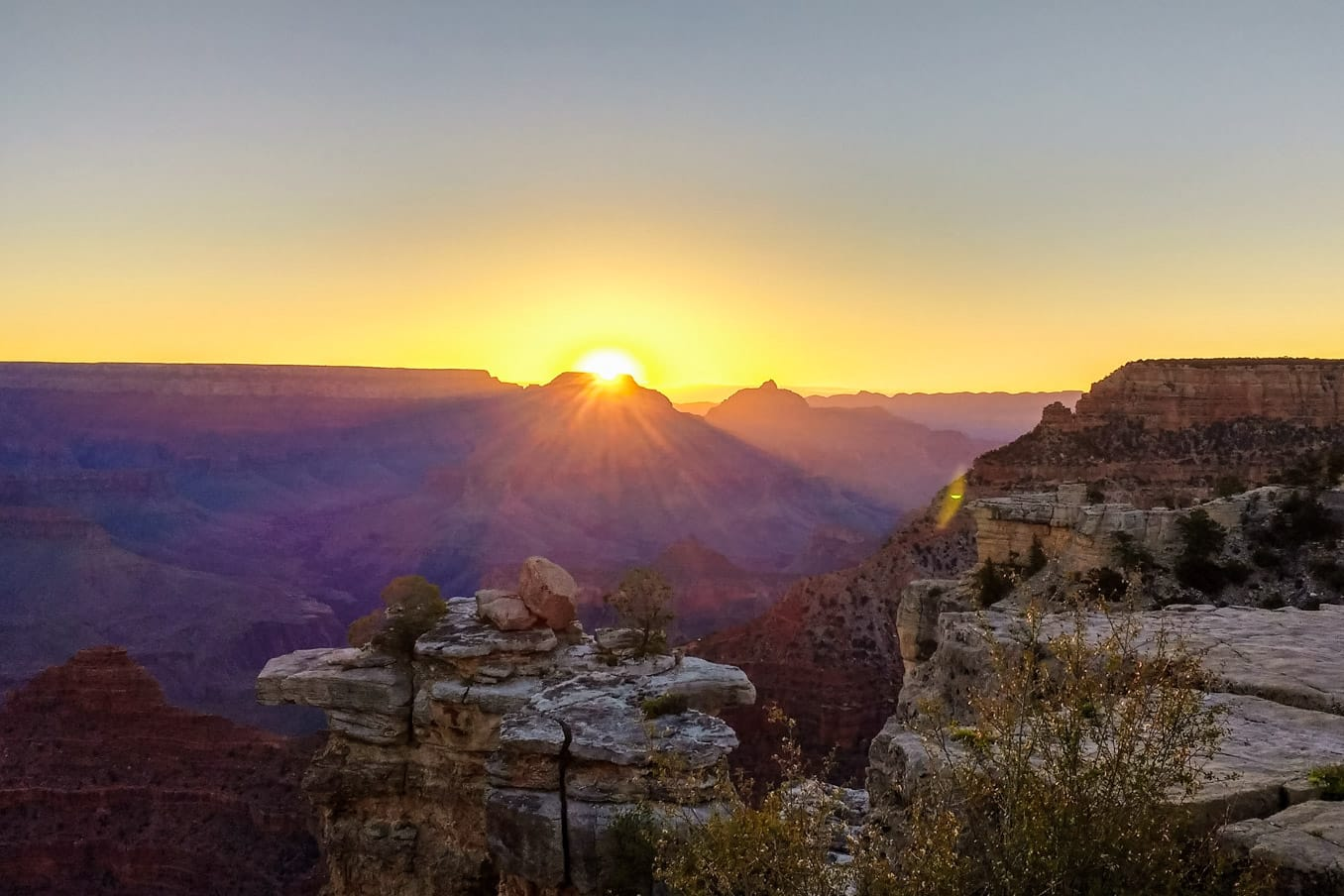 Sun sets behind overlook view of Grand Canyon.