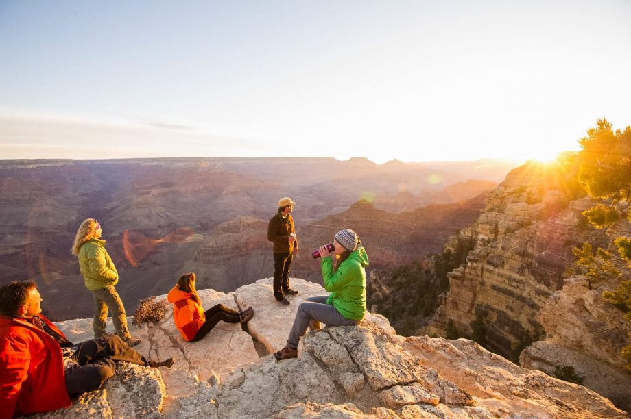 Hikers sit to watch the sunrise on Grand Canyon backpacking trip