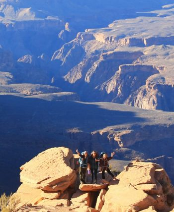 Hikers wave from Grand Canyon rocky overlook