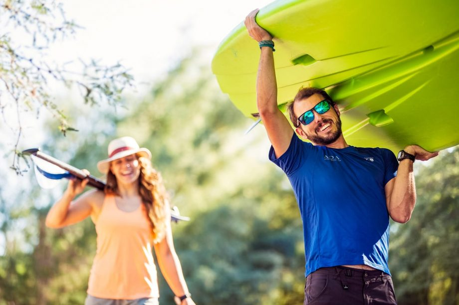 Man carries stand up paddleboard for Saguaro Lake day tour