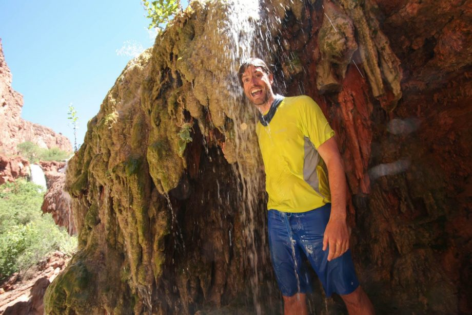 Hiker stands beneath Havasupai waterfall on backpacking trip