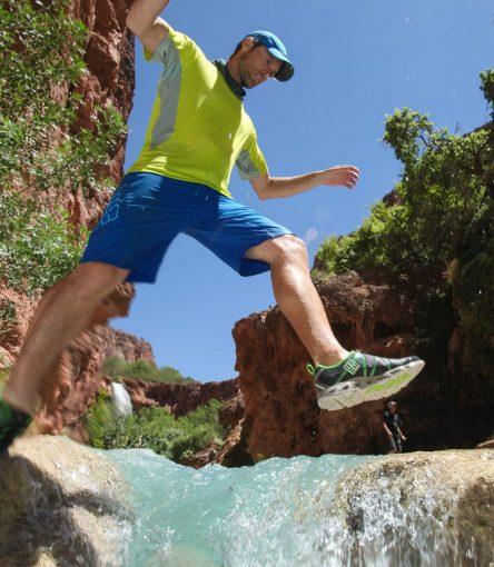 Hiker steps over small waterfall on Havasupai Falls trip