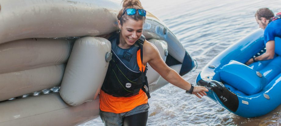 Smiling woman carries raft from water after kayaking tour