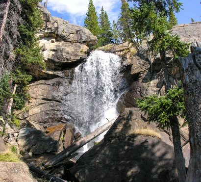 Waterfall rushes over cliff at Rocky Mountain National Park
