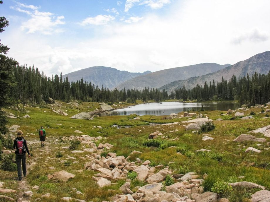 Hikers approach Rocky Mountain National park pond