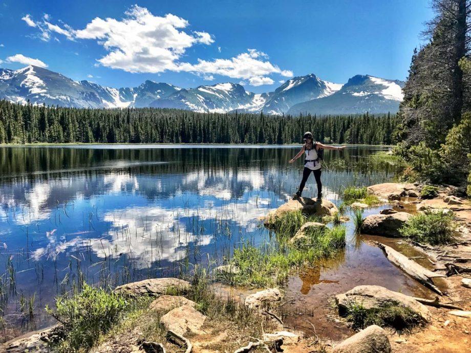 Hiker balances on rock next to reflective Rocky Mountain lake