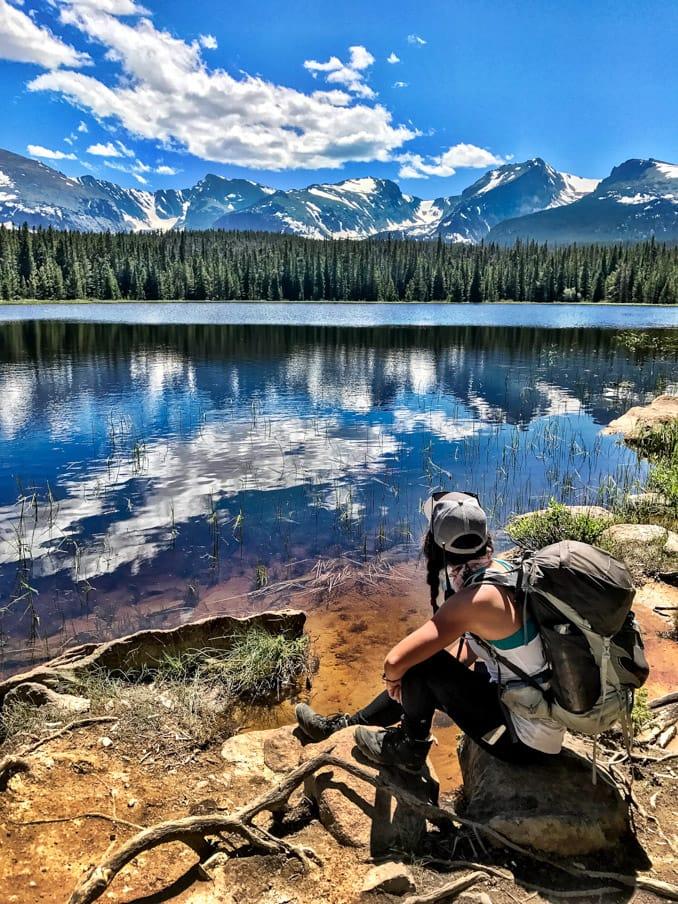 Hiker appreciates reflective lake on Rocky Mountain trip